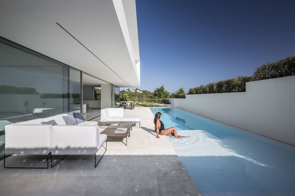 The water in the pool is level with the deck which enhances the continuity between all the different spaces