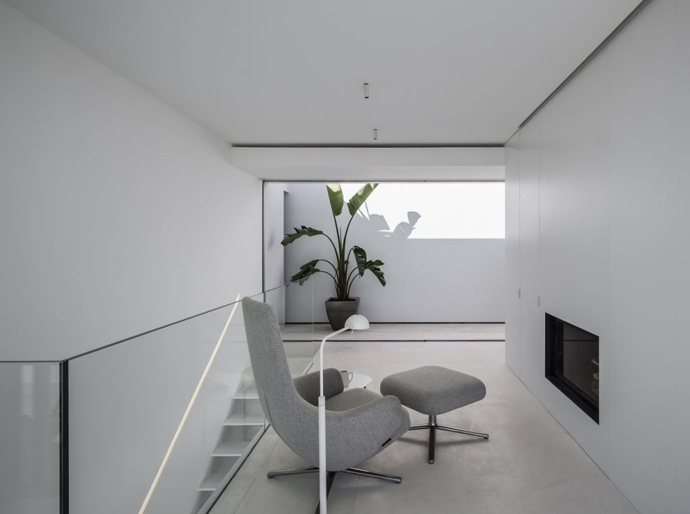 The interior design is minimalistic, with clean white walls, ceilings and concrete flooring throughout the house