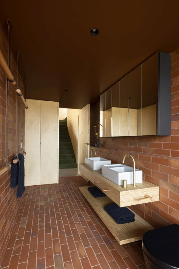 A red brick pattern and brown ceiling give the bathroom a warm and welcoming look