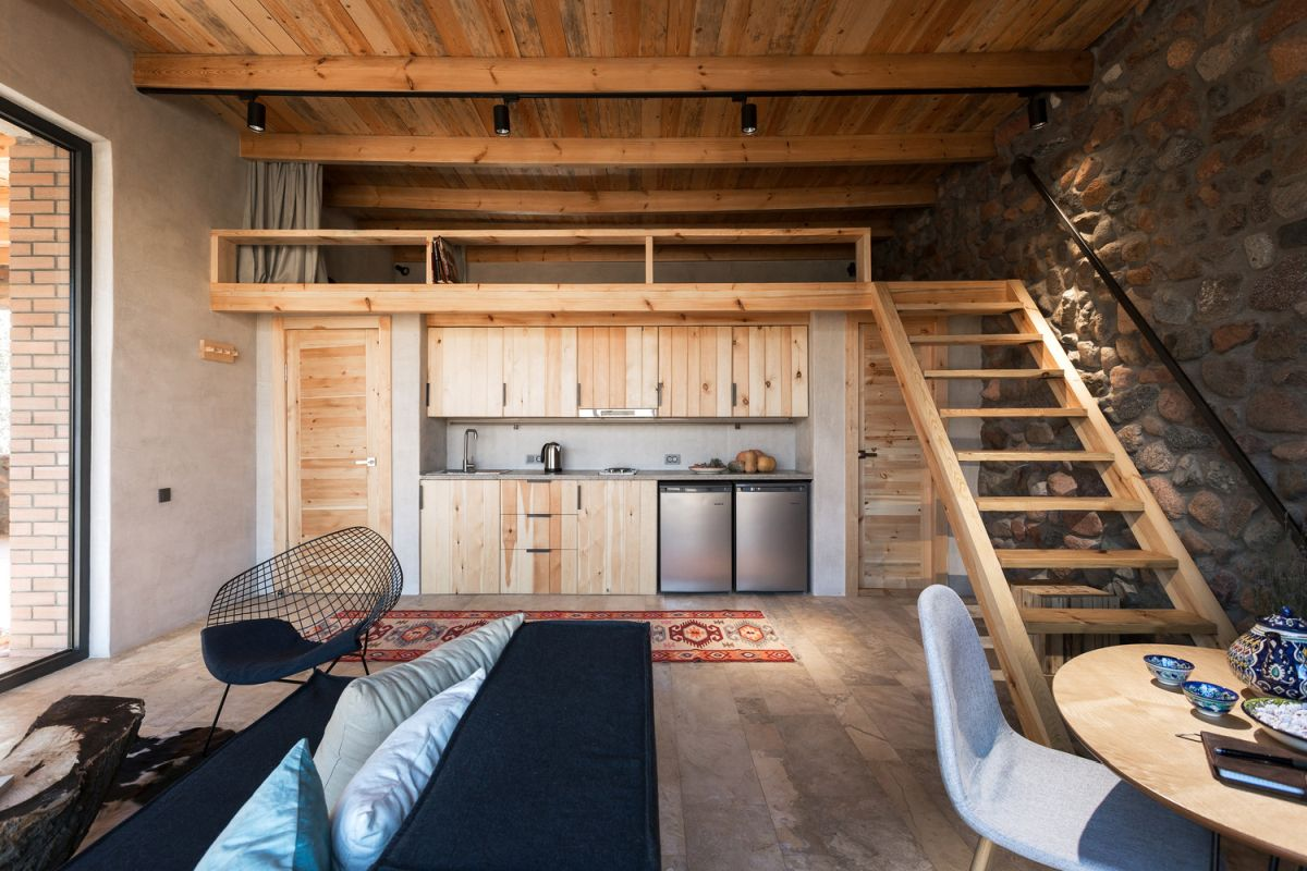 The interior of the house is simple and cozy, featuring stone surfaces complemented by wood
