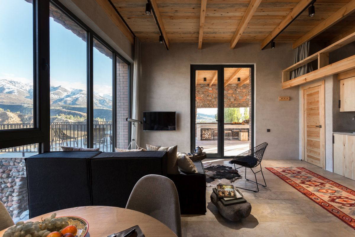 The interior design is defined by neutral and earthy colors and large windows that bring the outdoors in