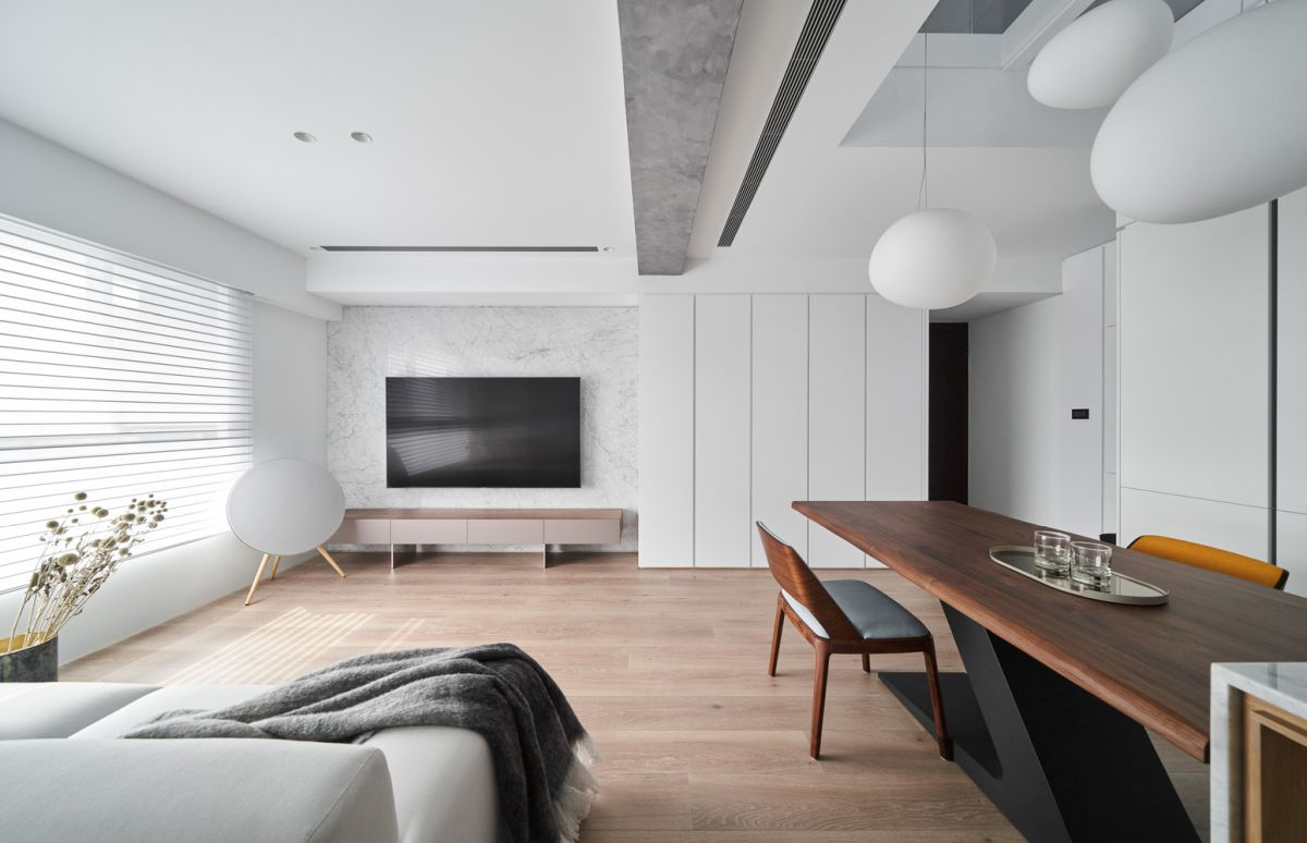 The living area has a large window with white blinds and an elegant TV wall with a white marble backdrop