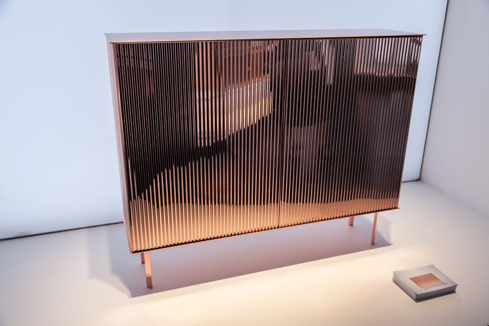 A small dresser with a polished copper finish