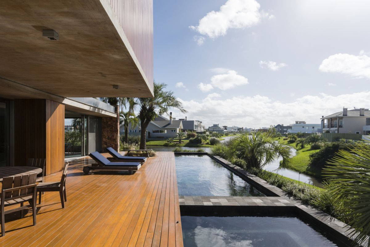 The living area can be seamlessly opened up onto the wooden deck and poolside area