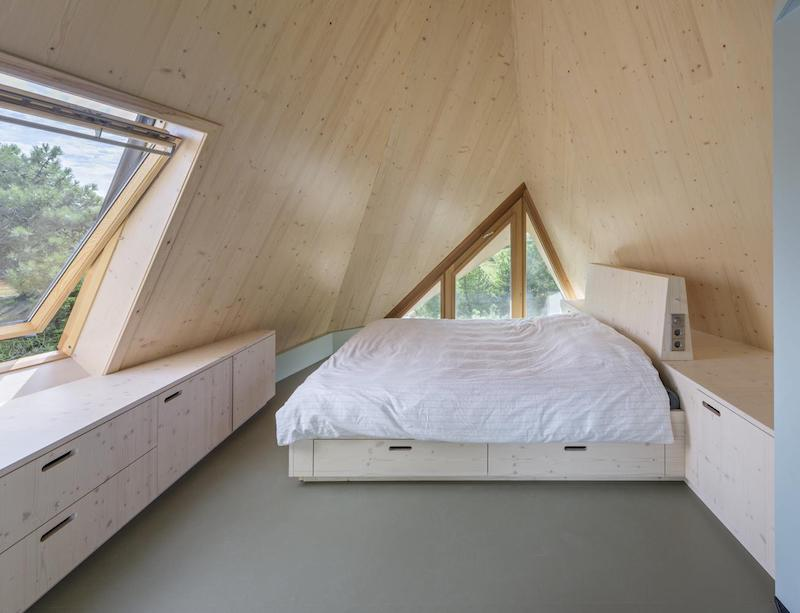The attic has small windows and slanted walls and ceilings which makes it feel very cozy