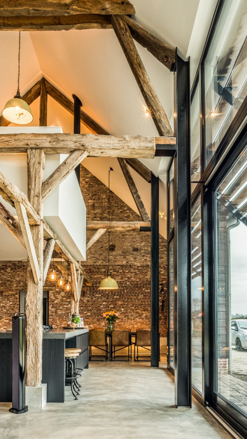 The wooden beams and brick wall give the house a rustic-industrial vibe and make it feel extra warm and cozy