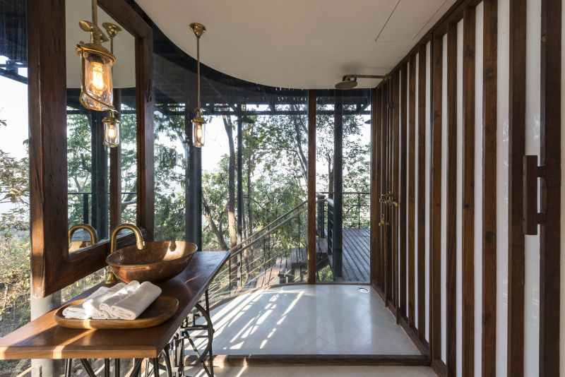 The bathroom is open to the outdoors too, featuring curved glass walls