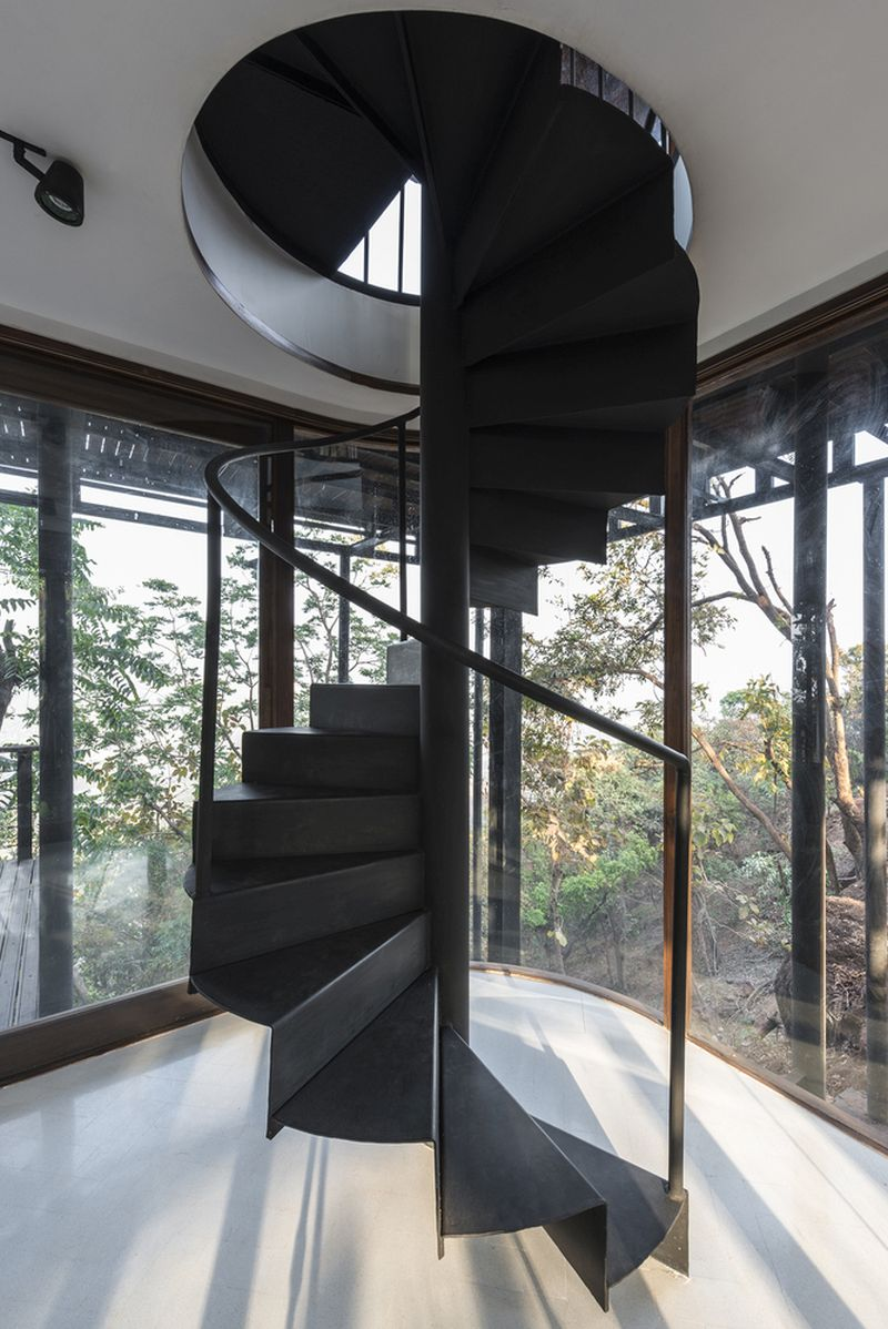 A spiral staircase offers access to a lower level where additional spaces can be found