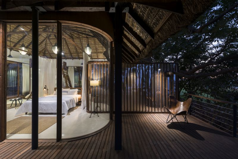 The wooden deck wraps around the interior spaces, complementing and protecting them