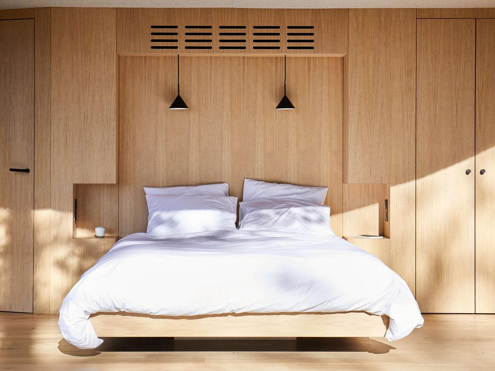 The interior area consists of a minimalist bedroom with a platform bed and built-in cabinetry