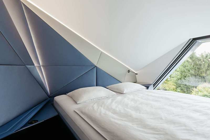 This cozy sleeping area is positioned right next to the window, under a sloped ceiling