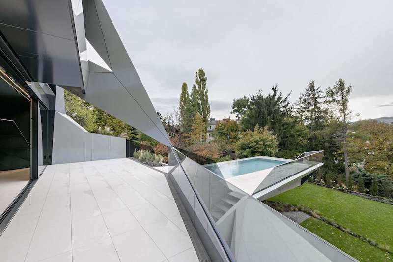 A swimming pool cantilevers over the garden,being framed by a small deck with glass railings