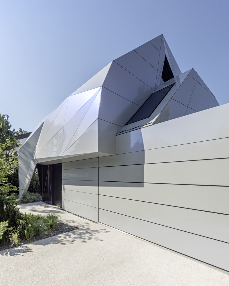 The angular, origami-like facade folds over the fence and gives the house a futuristic appearance