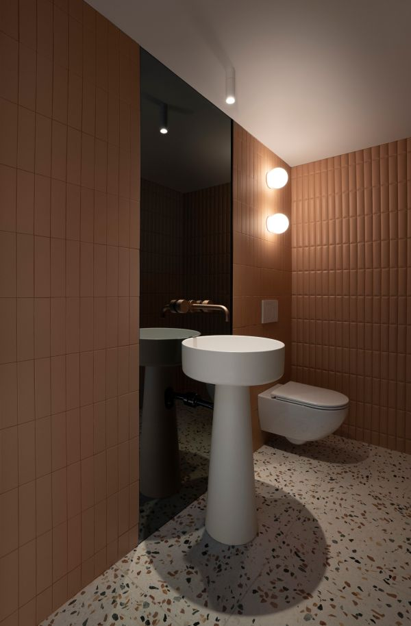 The metallic brown nuances and the ambient lighting give the powder room a really chic look
