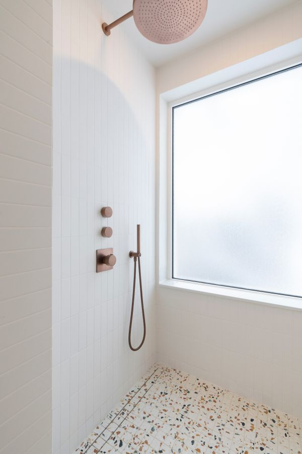 The copper fixtures add a chic and glamorous touch to the minimalist bathroom
