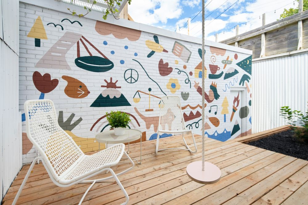 The backyard wall features a playful mural design with lots of lovely colors