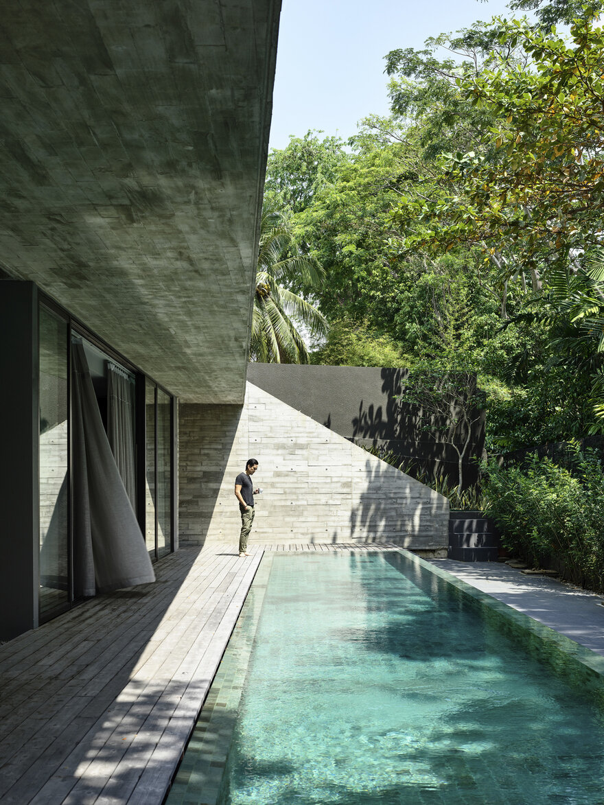 The open area at the back of the house is shielded by concrete walls and lush greenery