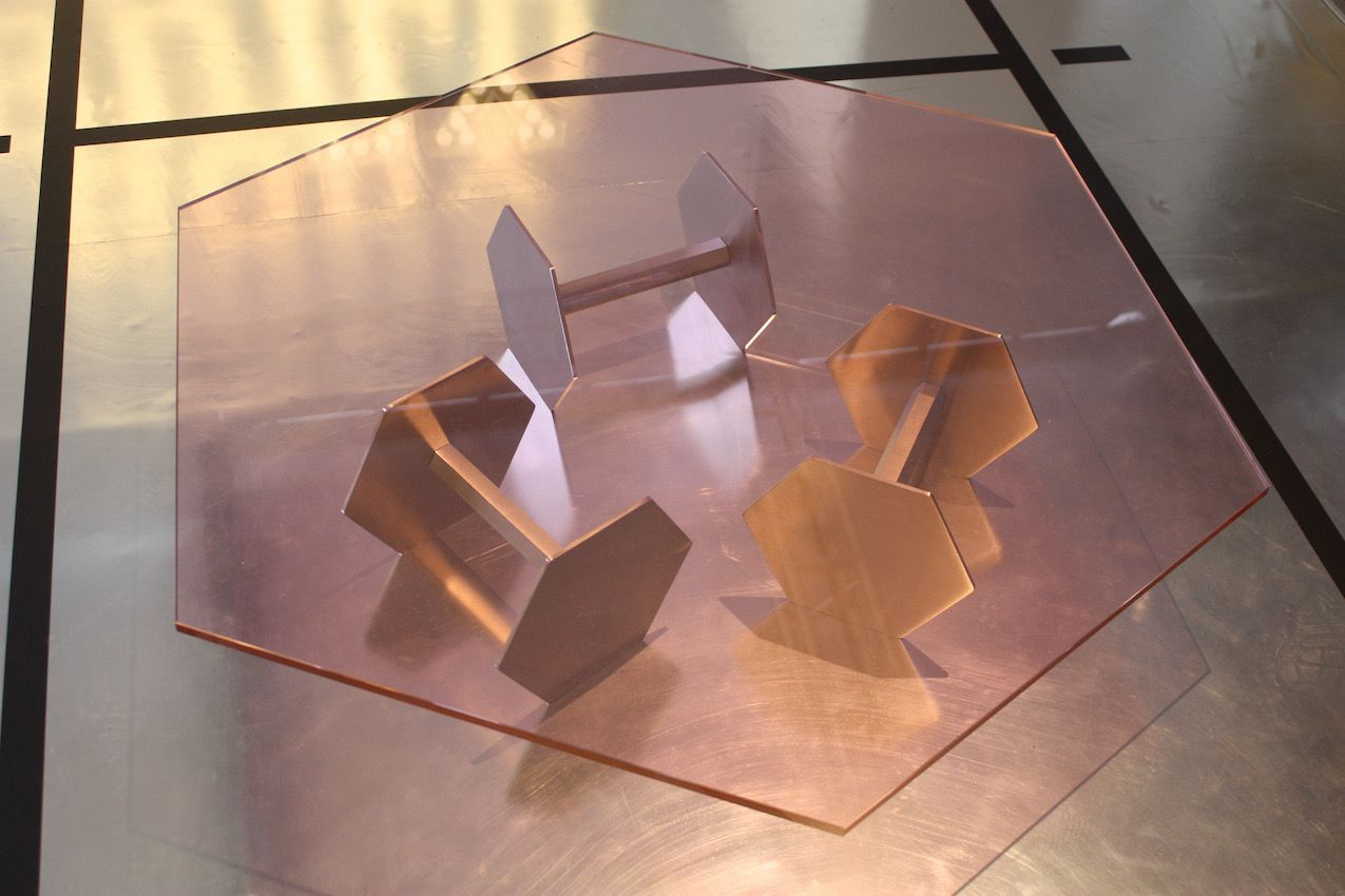 Glass-topped tables are nothing new but this appealing piece combines an unusual choice of pink glass with a base that plays on the concept of a gym and strength.