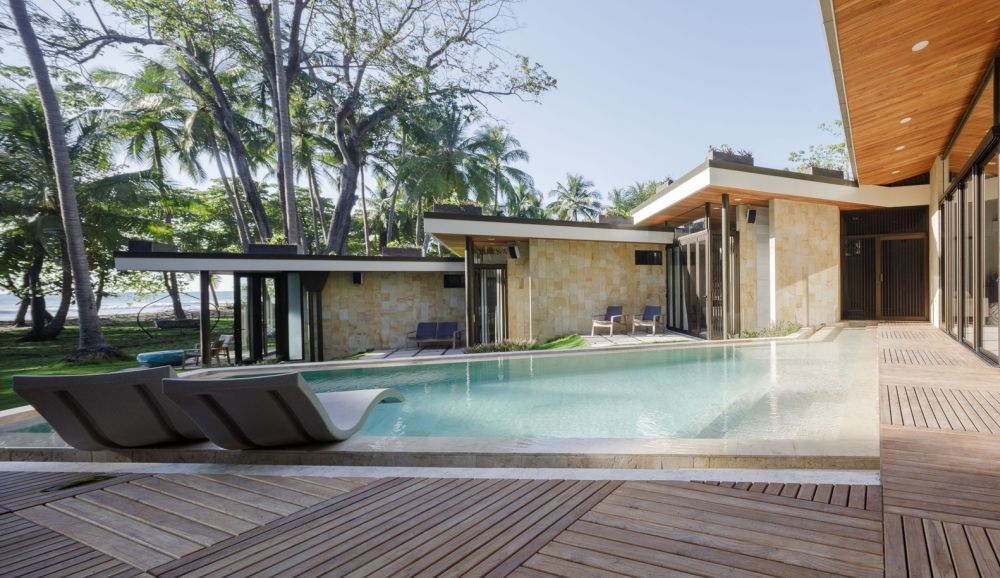 The swimming pool is framed by a wooden terrace that acts as a buffer between it and the houses