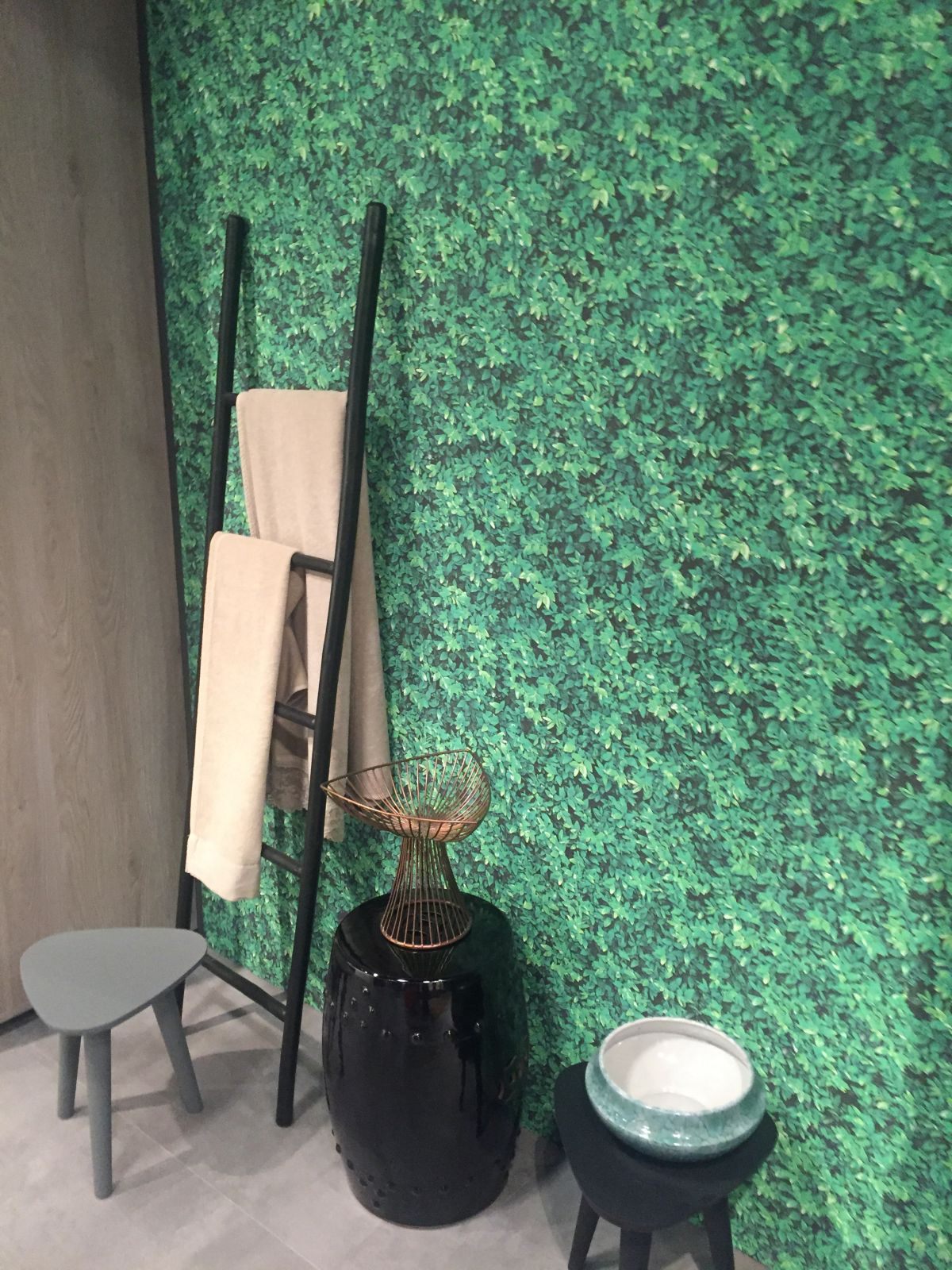 Green wallpaper for bathroom and ladder to towels