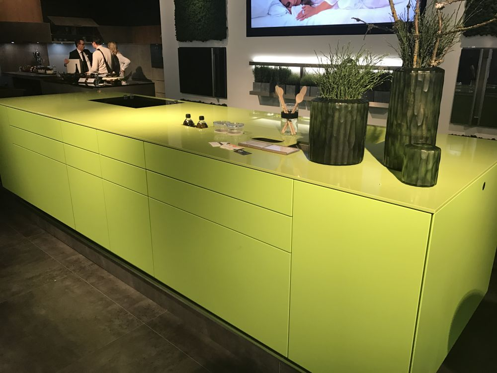 The light shade of green suits the minimalist island well and brightens up the kitchen