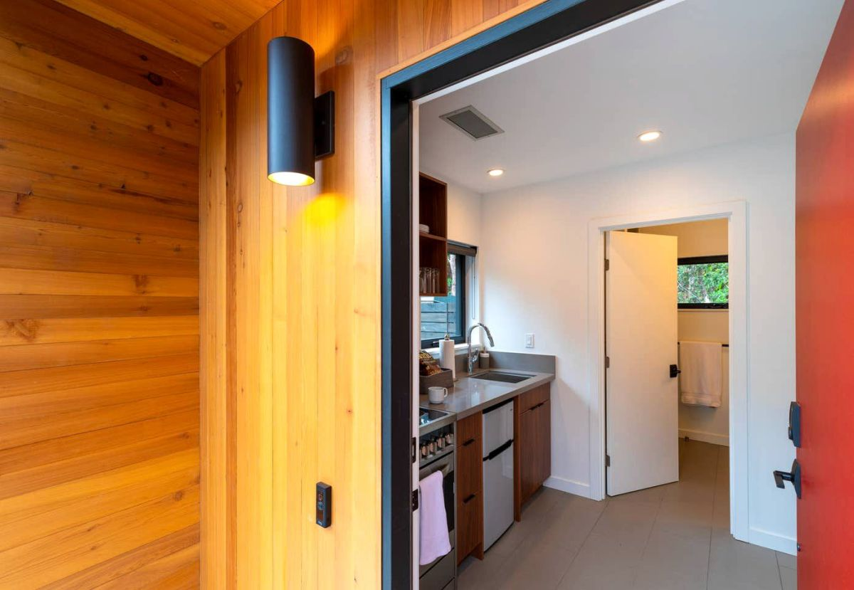 The cabin has a red front door which adds a bold touch to its design