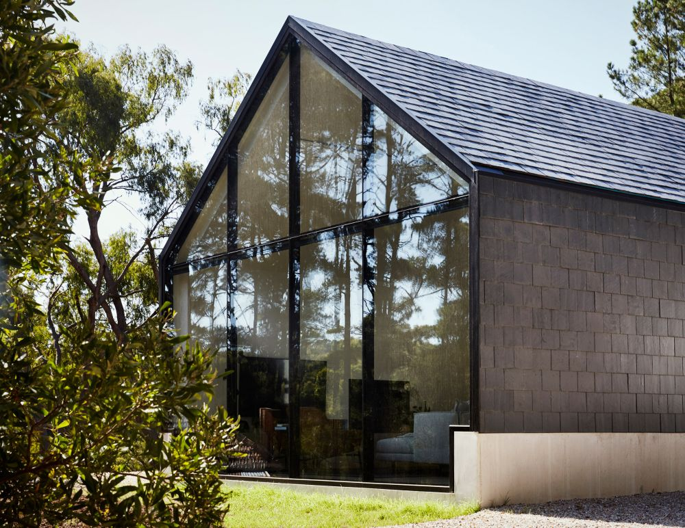 The larger volume has a gabled roof and large glazed walls
