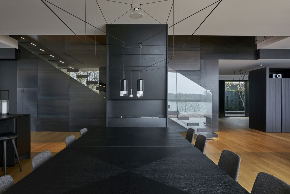 The kitchen and the dining area have a black-based color palette balanced out by the warm wooden floors