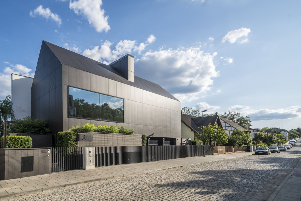 The roadside section of the house is closed to the street and has a minimalist black exterior