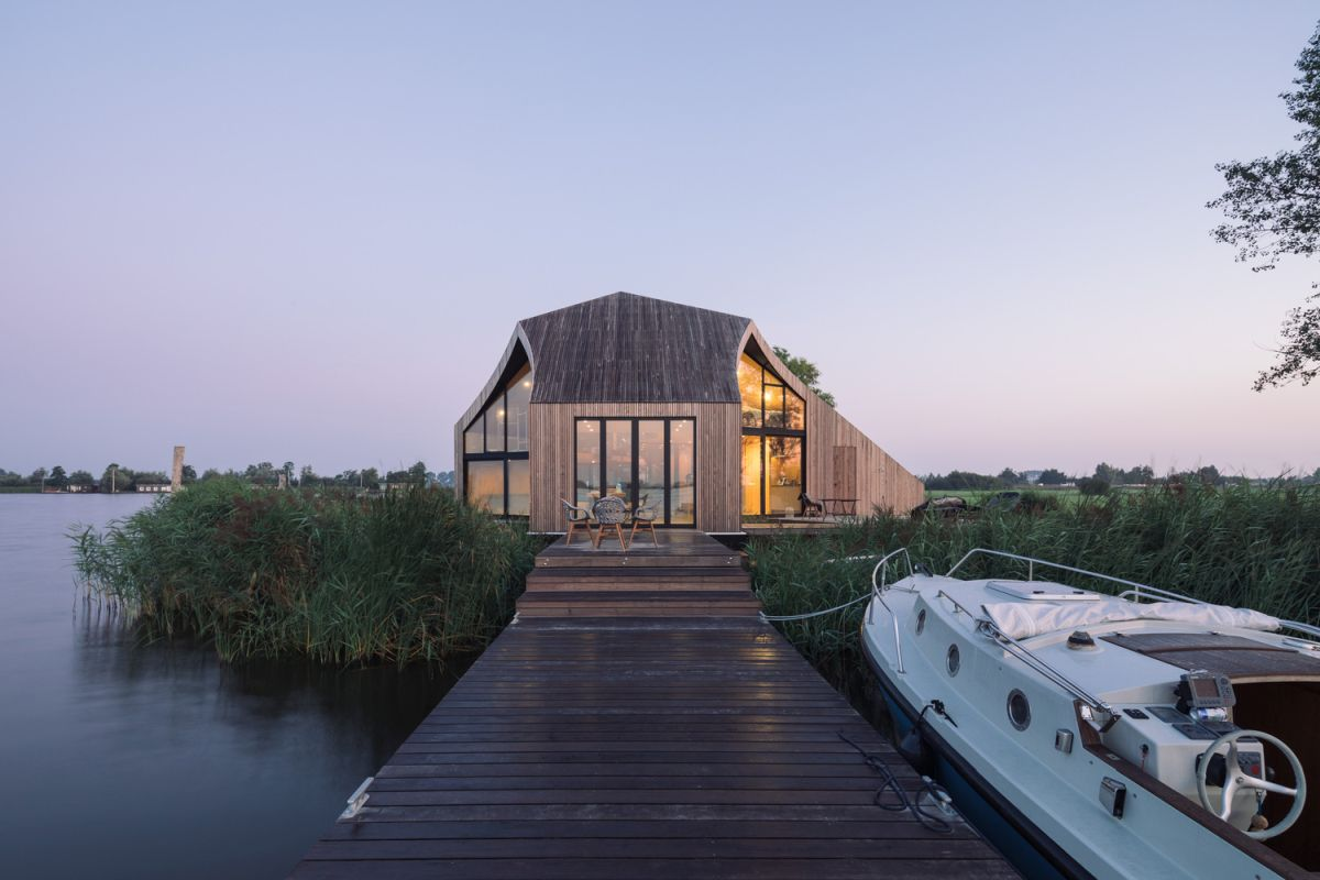 A small wooden dock extends at the back of the house