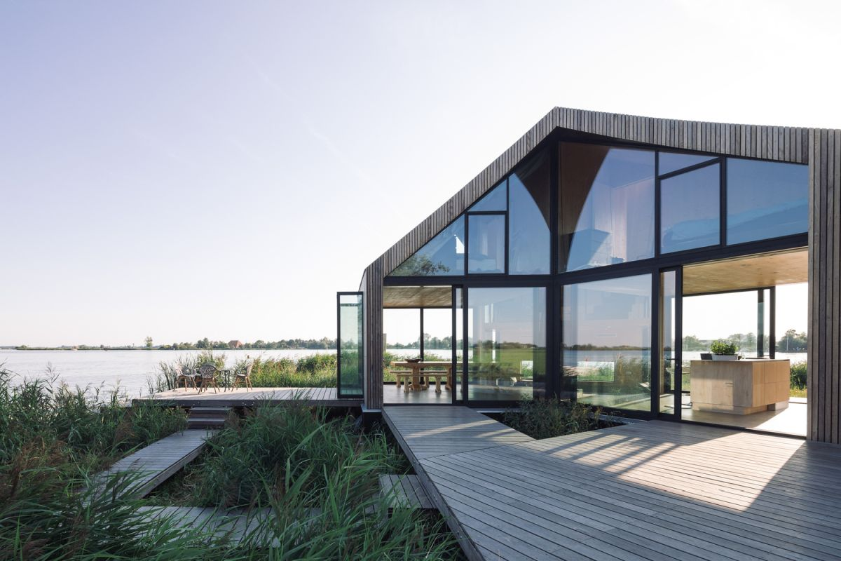 The interior spaces have full-height windows and open onto wooden deck areas