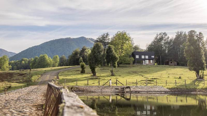 The site on which the house stands overlooks a lake and the mountain range in the distance