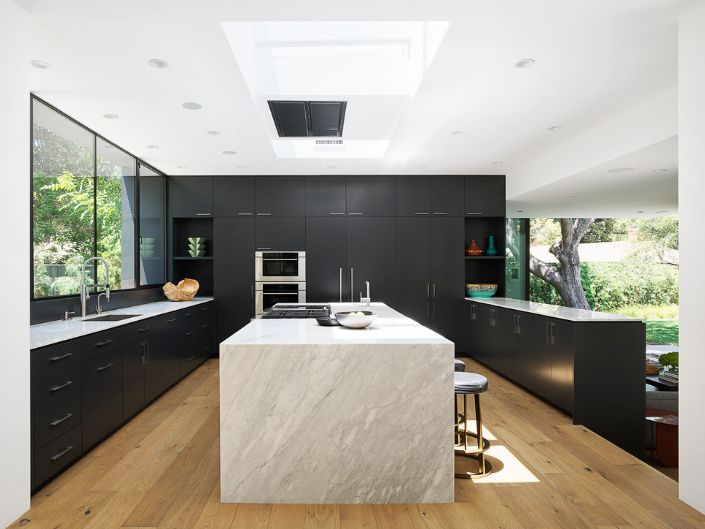 The kitchen is a bright and open space with black cabinets and an elegant white island