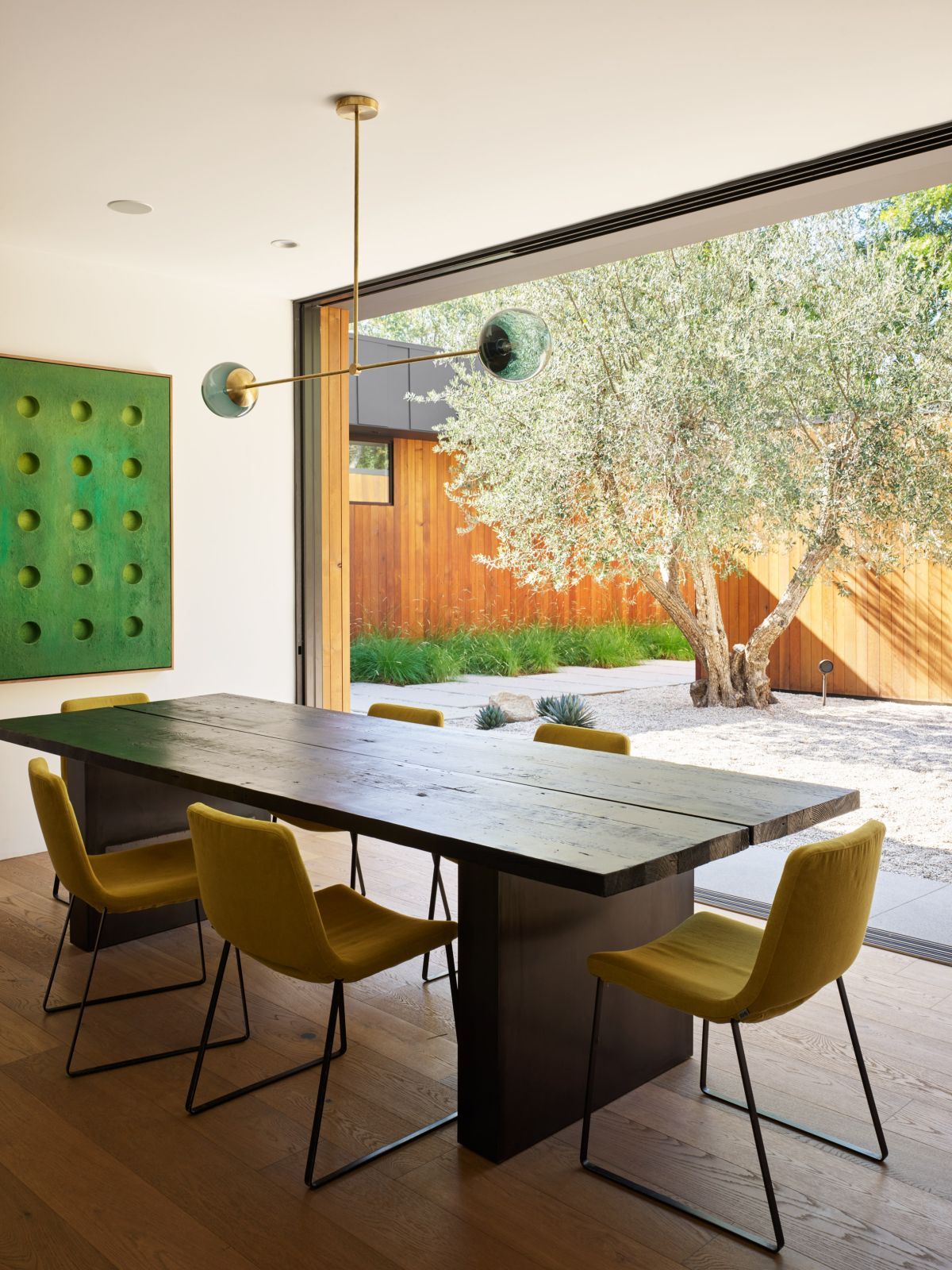 The dining room features a beautiful weathered wood table complemented by stylish yellow chairs