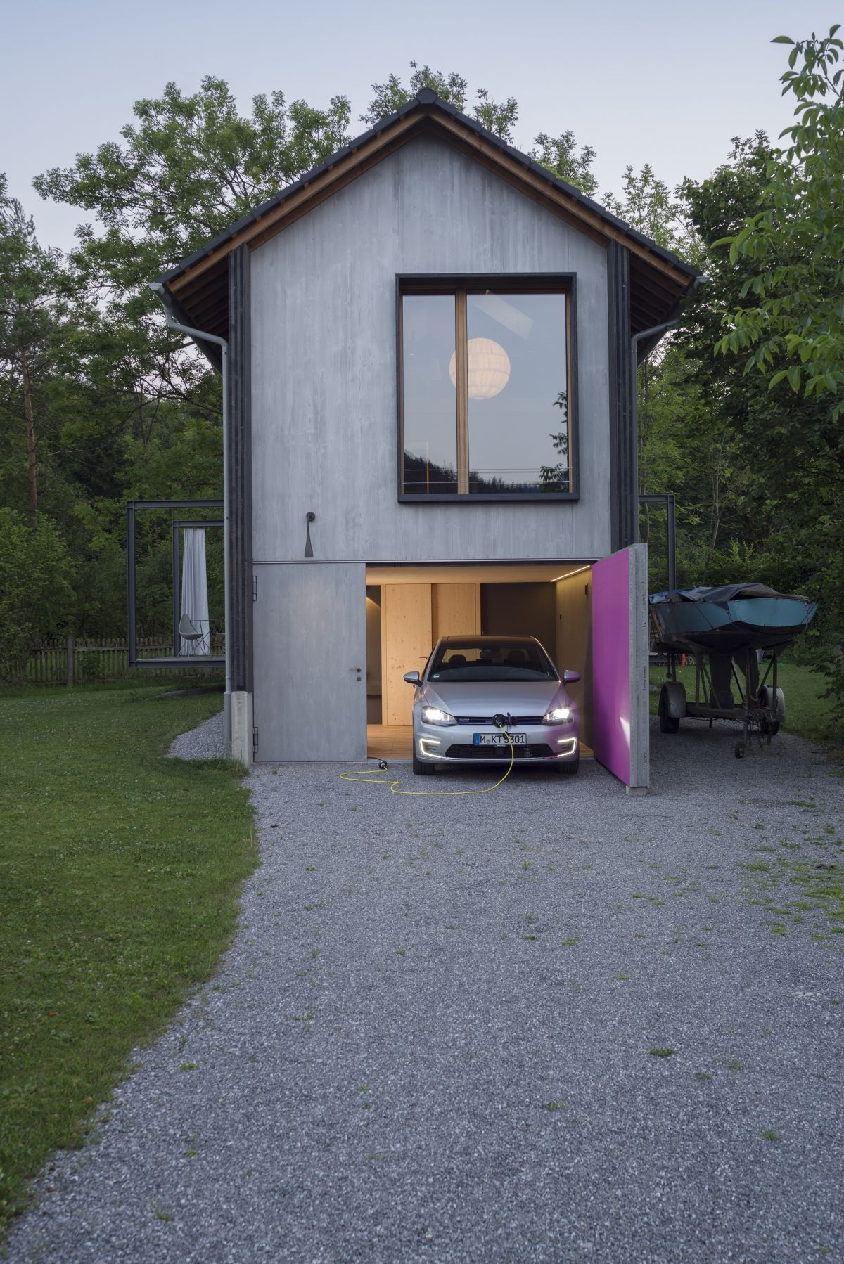 The large and very heavy garage door is bright pink on the inside, adding a quirky touch to the house