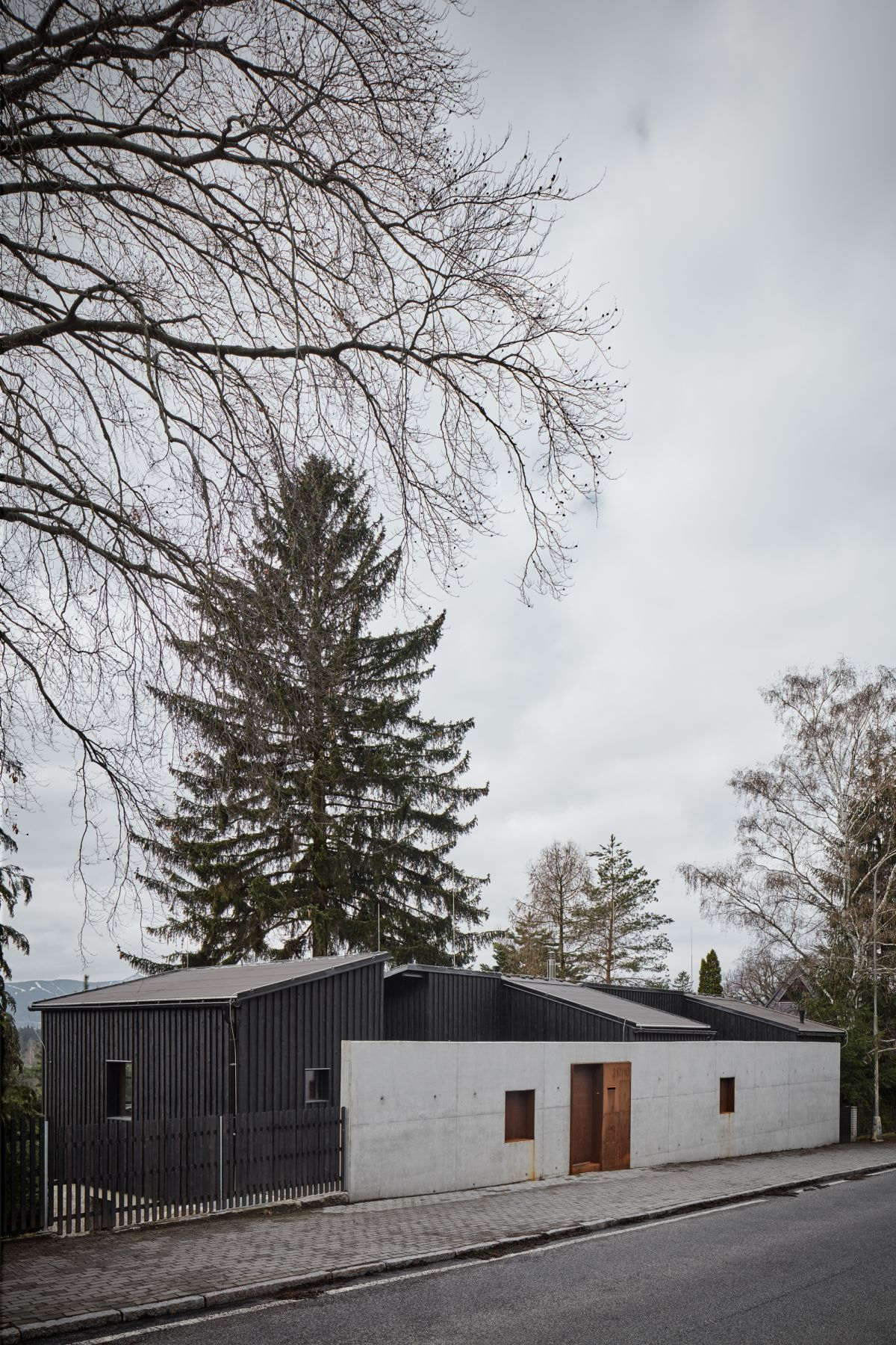 A concrete wall acts as a shield between the house and the road which borders it