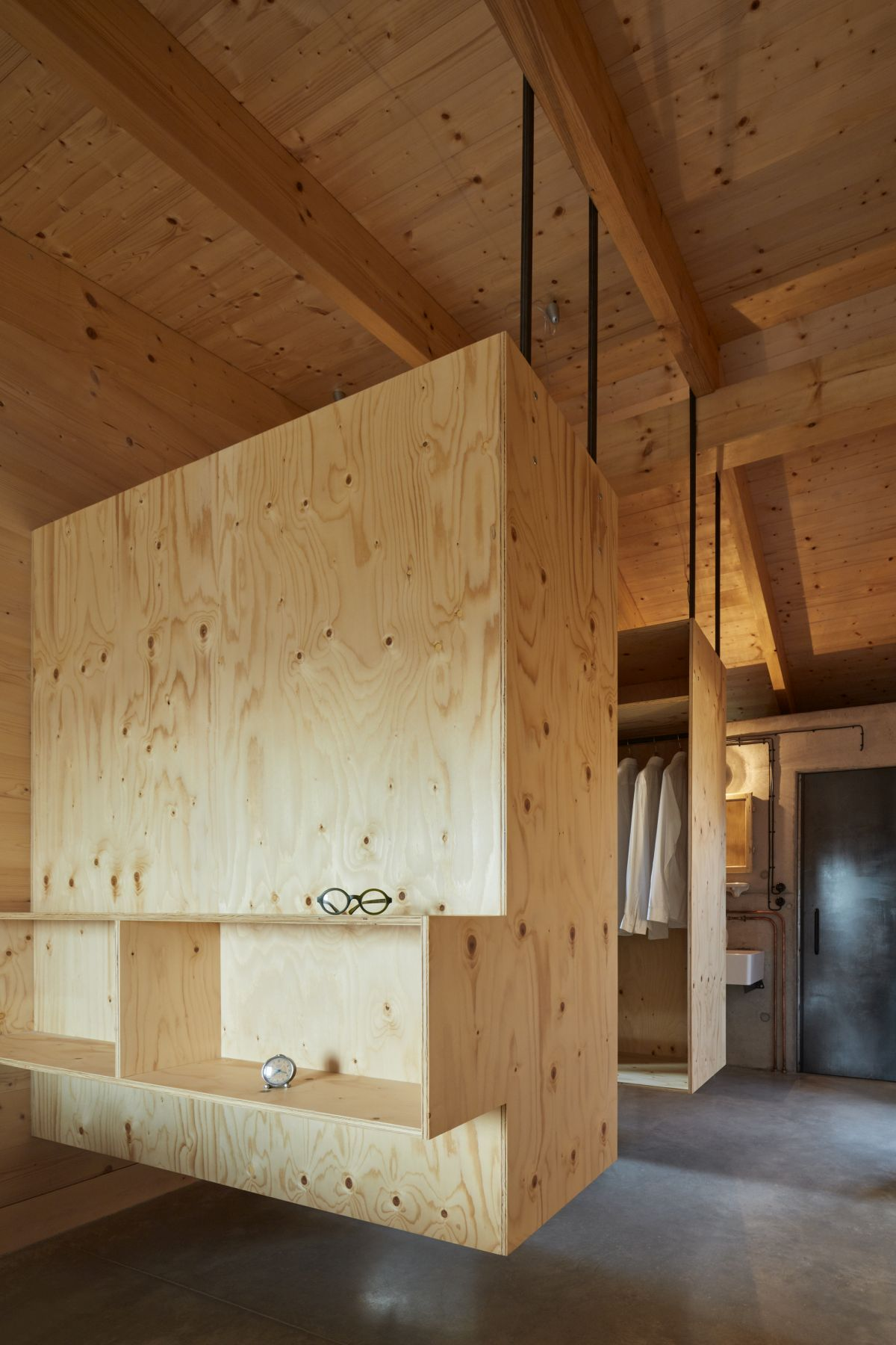 The master bedroom features wardrobe units hanging from the ceiling which saves floor space and creates an airy look