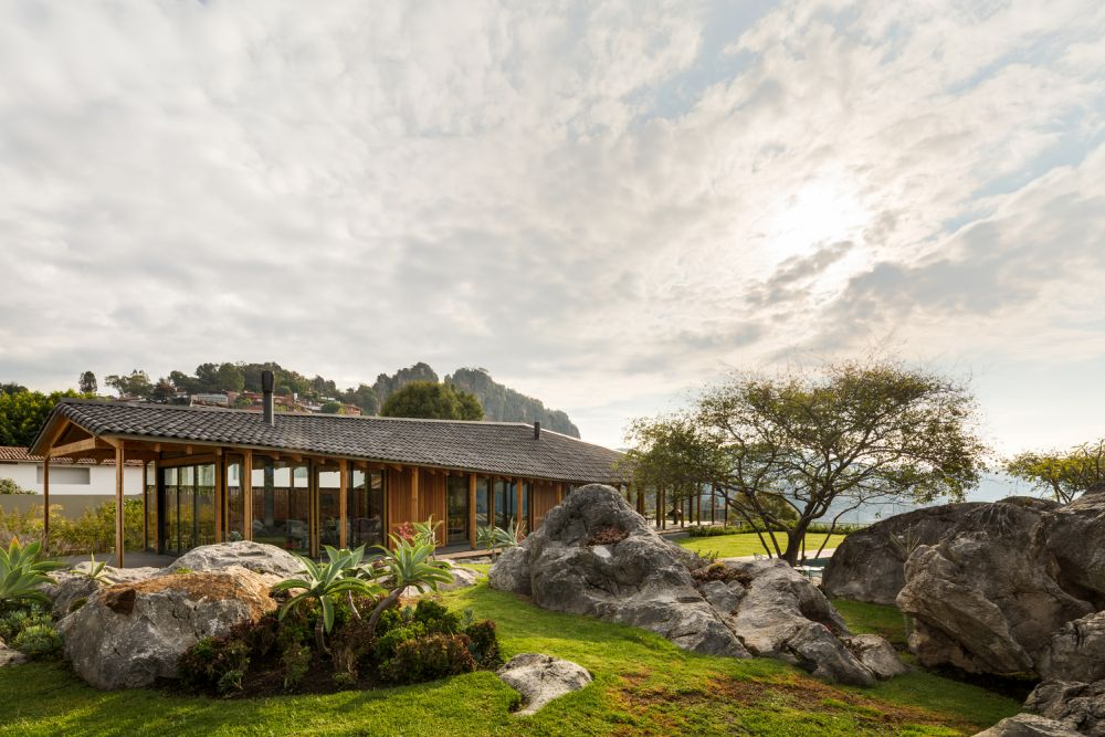 The living areas look perfectly at home among the boulders, grass and beautiful trees
