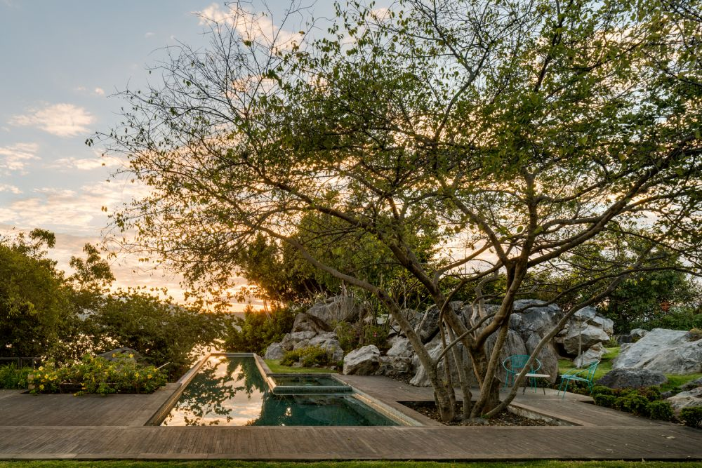 The wooden deck and the pool are seamlessly integrated into the land, seeking not to disturb nature but to coexist with it
