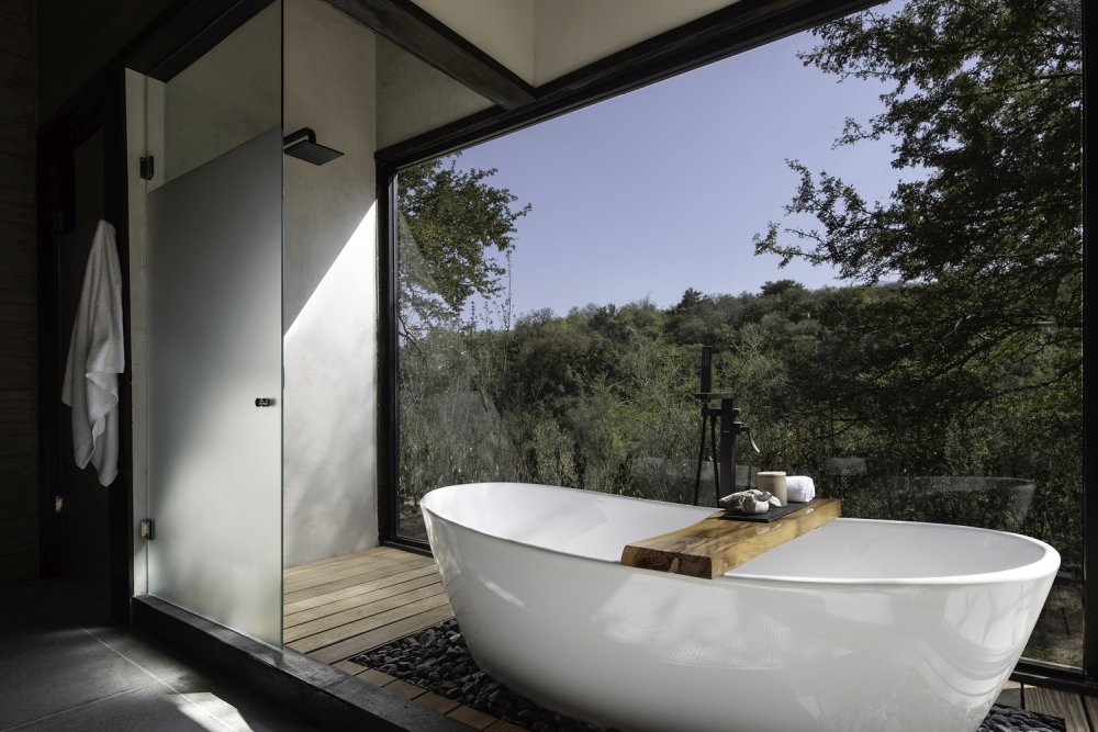 The bathtub and the shower are exposed to the landscape, creating the feeling of being outside
