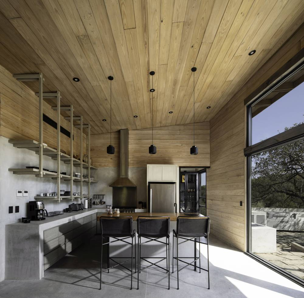 The interior of the cabin is simple and cozy, taking advantage of the large windows and the views