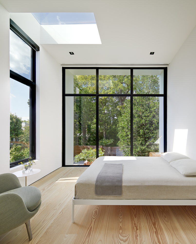 The new master bedroom occupies the second floor of the extension and has a ceiling skylight