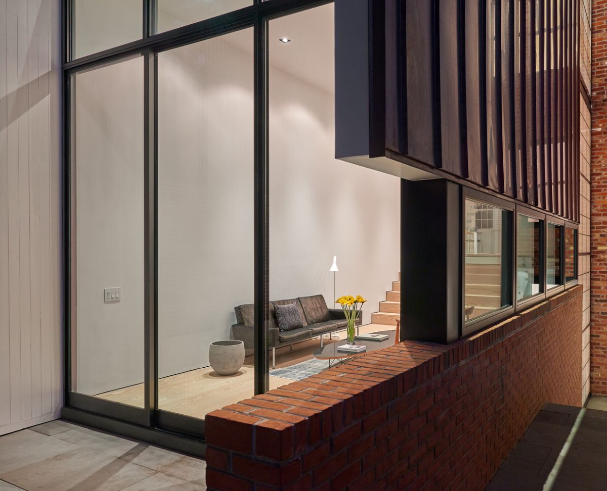 Exposed brick and stone are incorporated into the extension, as if the old structure is seeping into the new one