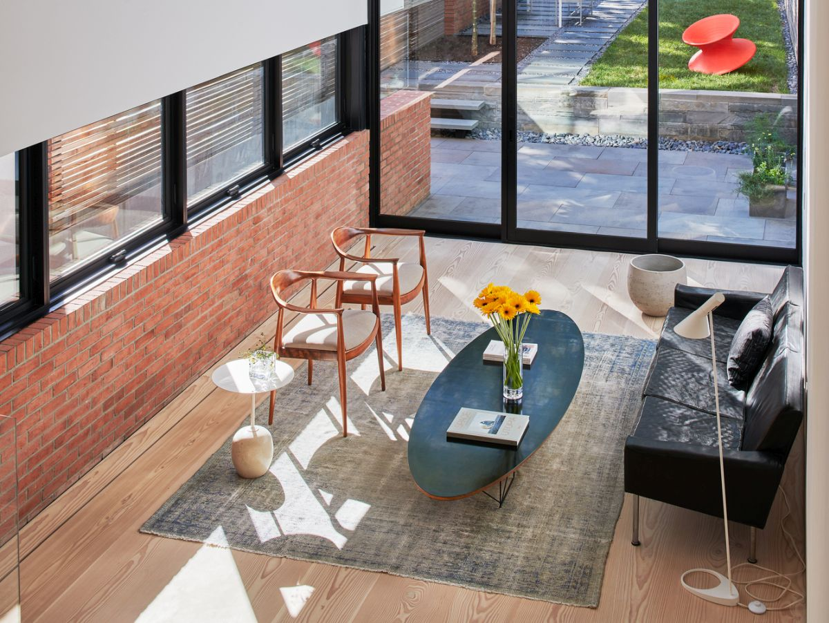 The ground floor of the newly added extension houses a cozy living room with an oval coffee table