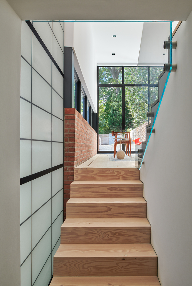 A wooden staircase leads down to the basement where the kitchen was originally situated