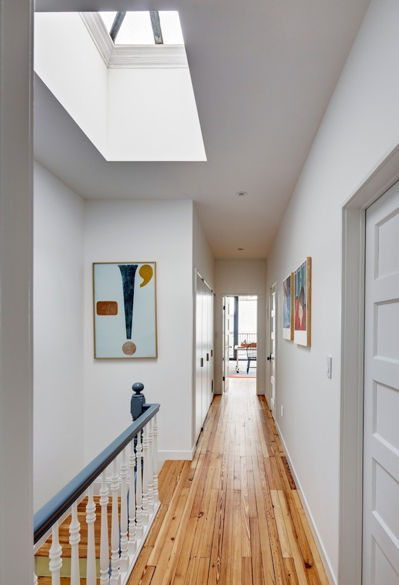 Upstairs, a hallway connects the spaces and brings in light through a skylight