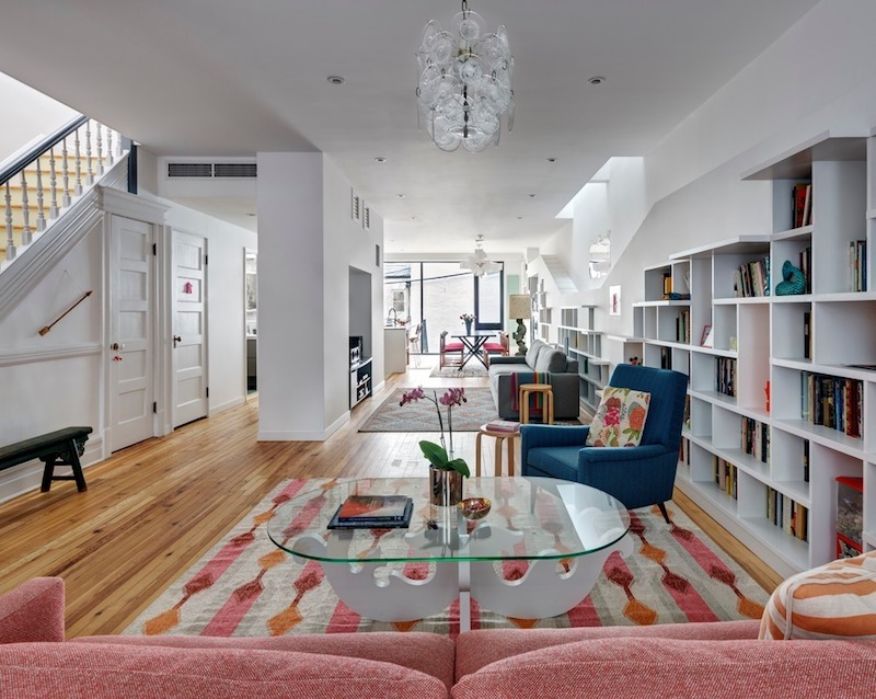 The bookcase runs along the entire length of the wall and holds an extensive book collection