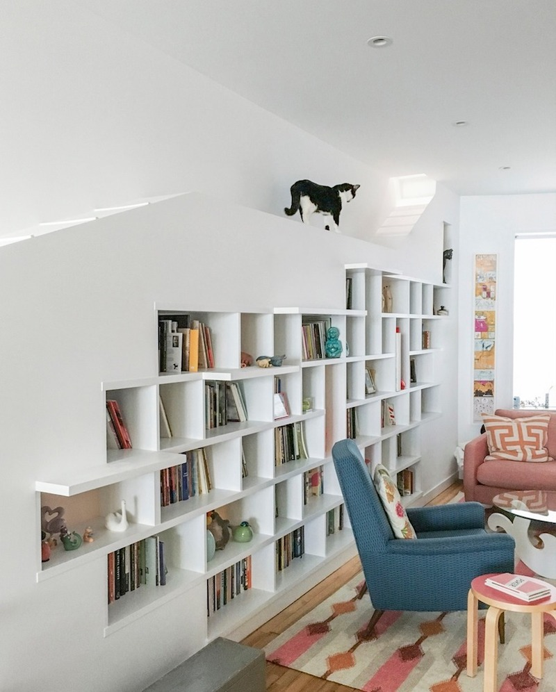 In the living room there's a custom bookcase wall with ramps for the two cats