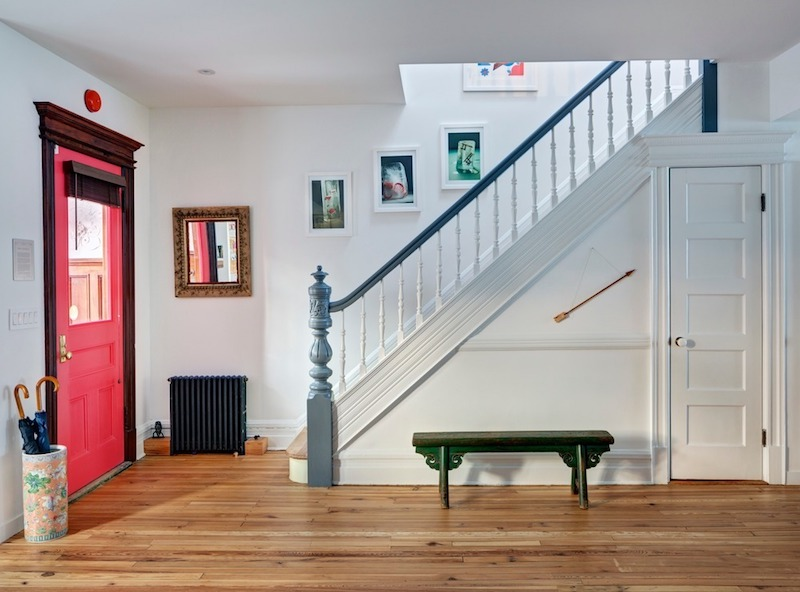 A staircase that leads upstairs is placed right in front of the entrance door