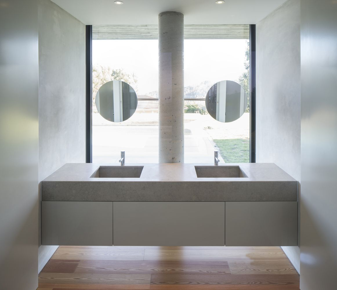 A combination of exposed concrete, wood and stone was used for the interior surfaces of the house